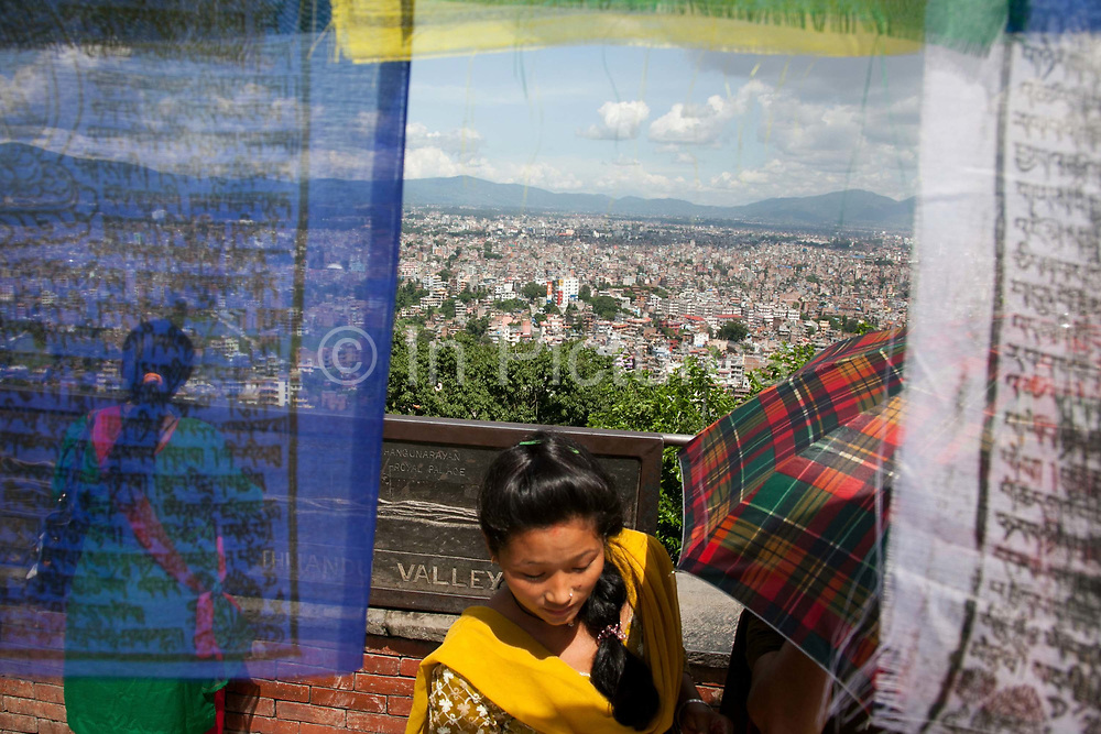 Visitors to the Swayambhunath temple complex, also called the Monkey Temple are enjoying the view of Kathmandu and the valley.