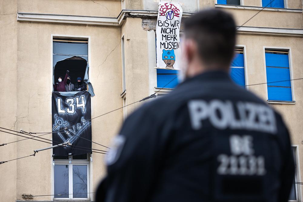 Am Rande einer Demonstration gegen die vor sechs Monaten durchgeführte Räumung des anarcha-queer-feministischen Hausprojekts Liebig 34 besetzten Aktivisten das Haus Türrschmidtstraße 1 in Berlin Lichtenberg als Protest gegen spekulativen Leerstand. Laut Demonstranten steht das Gebäude seit 14 Jahren leer. Nach mehreren Stunden räumt die Berliner Polizei die Besetzung. Ein Polizist vor dem besetzten Haus. Berlin, Deutschland, 10.04.2021.<br /> <br /> [© Christian Mang - Veroeffentlichung nur gg. Honorar (zzgl. MwSt.), Urhebervermerk und Beleg. Nur für redaktionelle Nutzung - Publication only with licence fee payment, copyright notice and voucher copy. For editorial use only - No model release. No property release. Kontakt: mail@christianmang.com.]