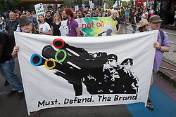 © licensed to London News Pictures. London, UK 28/07/2012. Protester posing with placards and banners against the defence precautions as anti-Olympics protesters marching from Mile End Park to Victoria Park in order to protest against the greed of the Olympic sponsors. Photo credit: Tolga Akmen/LNP