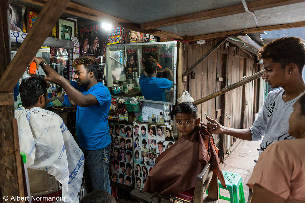 Barber shop in City Market area, with young boy customer, Mawlamyine