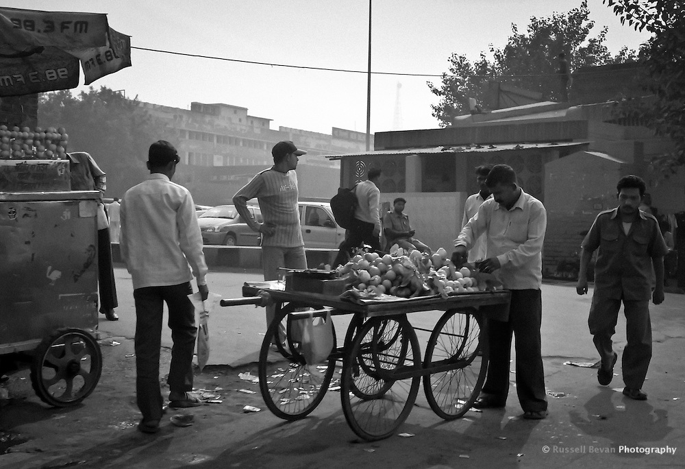 A man sells fruit from his cart on the street in Delhi, India