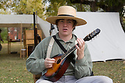 Arkansas, AR, USA, Old Washington State Park, Civil War Weekend A young boy playing a mandolin to entertain the troops