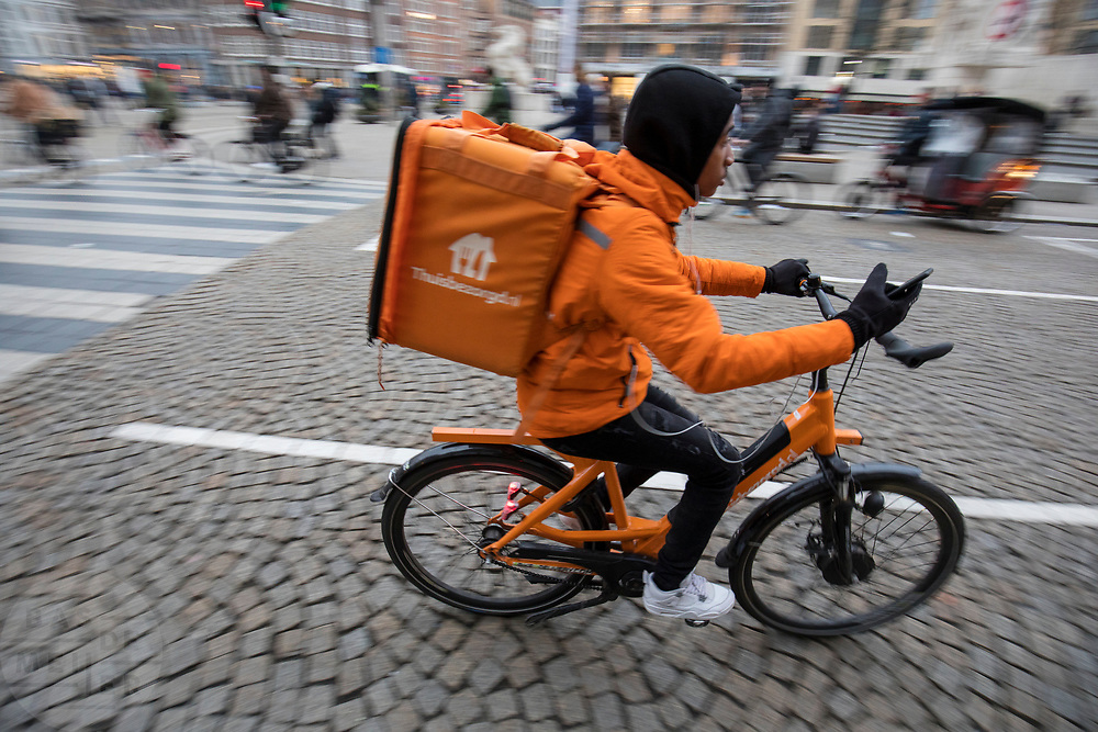 Een bezorger van Thuisbezorgd.nl rijdt met de telefoon in zijn hand op een oranje elektrische fiets over de Dam in Amsterdam.<br /> <br /> A food delivery boy rides on an electric bike with a phone is his hand at the Dam square in Amsterdam.
