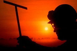 Silhouetted onshore oilfield worker at sunset.