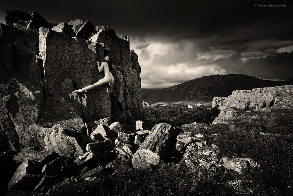 Nominated for 11th International B&W Spider Awards<br /> <br /> <br /> After a two hour slog up from sea-level valley to mountain top, loaded with photo gear & warm clothing, we were made to feel humble by a young woman climbing nude to the summit itself. Her pale soft skin contrasted with the sharp, rough rock but with such purpose, grace and balance, as if a slow motion dance, we could see her muscles working as she pulled, stepped into and lay-backed the arete before standing tall at the highest point to feel the cool mountain-top breeze caressing her hot skin. Below her, we huddled up and drank coffee and ate sandwiches.