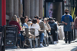 © Licensed to London News Pictures. 17/04/2021. Manchester, UK. Drinkers enjoy the sunshine on the first weekend since hospitality reopened in the city. Photo credit: Kerry Elsworth/LNP