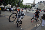 A youth performs a dangerous wheelie while riding on the wrong side of the road during a mass ride-through the West End,  on 19th August 2017, in London, England.