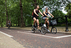 © Licensed to London News Pictures. 15/06/2021. London, UK. Members of the public cycle during sunny weather in St James's Park in Central London. Temperatures are expected to rise with highs of 25 degrees forecasted for parts of London and South East England today . Photo credit: George Cracknell Wright/LNP
