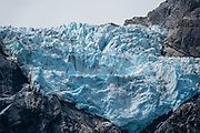 """Queulat Hanging Glacier, in Queulat National Park, Aysen Province, Chile, Andes mountains, Patagonia, South America. Queulat Hanging Glacier, the park's centerpiece, extends from the Queulat ice cap, which borders the northernmost part of the Puyuhuapi Channel called Ventisquero Sound (actually a fjord, carved by glaciers). Sendero Ventisquero Colgante, the best trail in the park, reaches Mirador Ventisquero Colgante (Viewpoint of Queulat Hanging Glacier). Hike 4 miles or 6.6 km round trip with 1150 ft ft or 350 m cumulative gain. Cross a suspension bridge (where the limit of 4 people at a time can cause significant waits). Walk a rocky and rooty yet popular trail through dense forest. Go early in the morning to avoid crowds. The park is one of the rainiest places (3500 - 4000 mm) in Chilean Patagonia. Ventisquero (or """"snowdrift"""") is an archaic word for """"glacier"""" used by early South American explorers."""