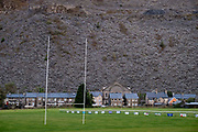 A mountain of slate dominates a rugby field, terraced housing and a church, on 3rd October 2021, in Blaenau Ffestiniog, Gwynedd, Wales. The derelict slate mines around Blaenau Ffestiniog in north Wales were awarded UNESCO World Heritage status in 2021. The industry's heyday was the 1890s when the Welsh slate industry employed approximately 17,000 workers, producing almost 500,000 tonnes of slate a year, around a third of all roofing slate used in the world in the late 19th century. Only 10% of slate was ever of good enough quality and the surrounding mountains now have slate waste and the ruined remains of machinery, workshops and shelters have changed the landscape for square miles.