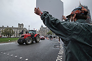 People hold placards and banners during a Farmers with Tractors protest over food and farming standards in London on Monday, Oct 12, 2020. Tractors travelled to Parliament in London as MPs vote on the Agriculture Bill, aimed at blocking the import of lower-standard produce.(VXP Photo/ Gio Strondl)