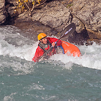 Play boat kayaker Lianne Germaine (MR) wave surfing on Kananaskis River, Kananskis Provincial Park, near Banff and Calgary, Alberta, Canada