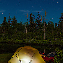 "Tent and canoe next to the Cold Stream ""deadwater"" above Upper Cold Stream Falls in Maine's Northern Forest. Night. Johnson Mountain Township."