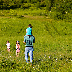 A man with his young daughter and her friends walk in a field in Sabins Pasutre in Montpelier, Vermont.