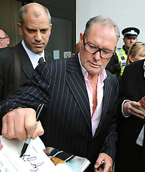 Former England footballer Paul Gascoigne signs autographs as he leaves Dudley Magistrates Court where he has been fined £1,000 for making a racist comment to a black security guard at a public event.