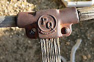 Close-up view of the cast metal handle of an antique PQ push-mower with an aged wooden handle shows a patent date of Feb 26, 1918.