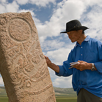 """Mongolian archaeologist Tovuudorj Sanjmyatov (""""Sasha"""") (MR) studies carvings on a 2700+ year-old, bronze age deer stone monument at Ulaan Tolgoi archaeological site near Lake Erkhel, north of Muren, Mongolia.   Sasha is a renowned pioneer of Mongolian archaeology, some of it pursued & published during Soviet era."""