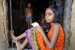 Barasha Sahoo, Age- 11 years, completes her homework in the doorway of her home.<br /> CLAP runs many programmes in this area to promote community rights and provide legal support for individuals and communities especially slum communities such as this that have no land rights.   Programme: Community Awareness Programme on Birth Registration. Dobandhanagar Community, Cuttack City, INDIA