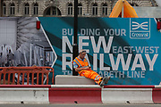 Construction workers rest in front of billboards promoting Crossrails new Queen Elizabeth rail line, the capitals newest  on 3rd September 2018, at Liverpool Street in London, England. Crossrails Elizabeth Line is a 118-kilometre 73-mile railway line under development in London and the home counties of Berkshire, Buckinghamshire and Essex, England. Crossrail is the biggest construction project in Europe and is one of the largest single infrastructure investments ever undertaken in the UK - a£15bn transport project that was due to open in December 2018 but now delayed to autumn 2019.