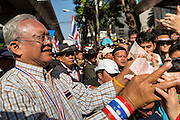 """15 JANUARY 2014 - BANGKOK, THAILAND: SUTHEP THAUGSUBAN, former Deputy Prime Minister of Thailand and leader of the Shutdown Bangkok anti-government protests, accepts cash from supporters on Sukhumvit Road in Bangkok during a protest march. Tens of thousands of Thai anti-government protestors continued to block the streets of Bangkok Wednesday to shut down the Thai capitol. The protest, """"Shutdown Bangkok,"""" is expected to last at least a week. Shutdown Bangkok is organized by People's Democratic Reform Committee (PRDC). It's a continuation of protests that started in early November. There have been shootings almost every night at different protests sites around Bangkok. The malls in Bangkok are still open but many other businesses are closed and mass transit is swamped with both protestors and people who had to use mass transit because the roads were blocked.    PHOTO BY JACK KURTZ"""