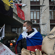A pro-Russia activist takes guard at the main entrance of Donbass Regional Government building in central Donetsk. Barricades around the building, occupied since the past weekend, have been fortified throughout the day, as the ultimatum given by the government in Kiev for the activists to abandon the building within 48 hours, is approaching its deadline.