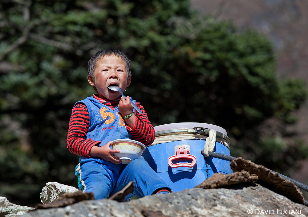 A boy having lunch along the path leading from Mongla to Phortse.