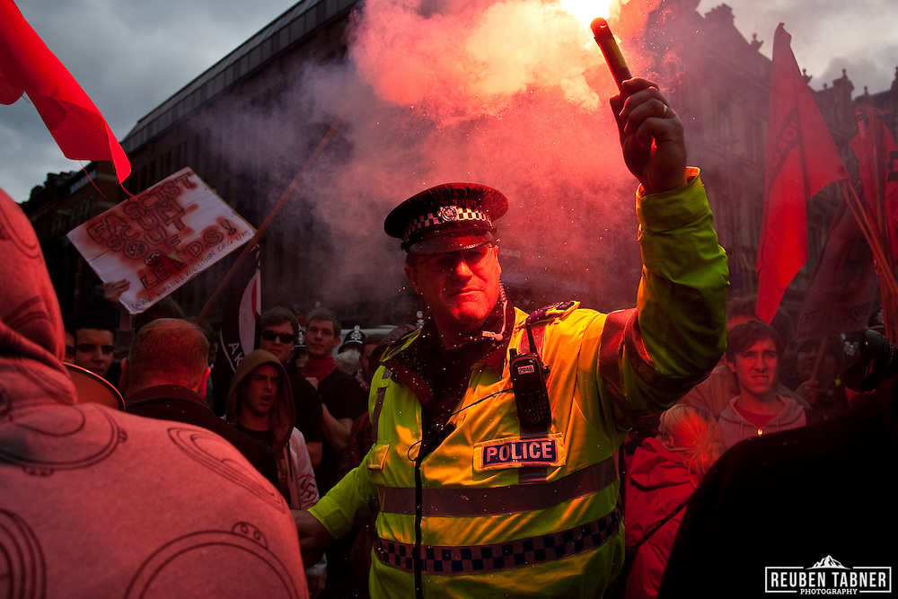 UAF supporters let of a flare, which is recovered by the police.