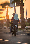 Rear view of couple on motorcycle going along street on Corniche at sunset, Casablanca, Morocco