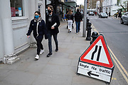 Single file traffic on the pavement in the upmarket area of Chelsea on 14th April 2021 in London, United Kingdom. Chelsea is one of the principal areas for exclusive, luxury goods in West London. It is known as a district where the rich and wealthy shop, mostly for high street and high end fashion and jewellery.