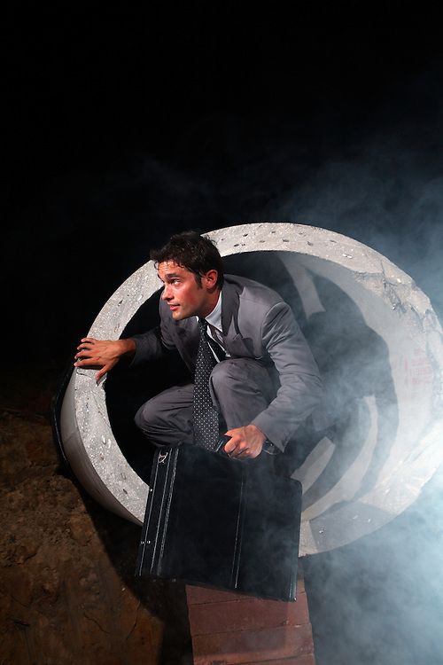 Willmington - JUNE 3: D. McIver wears a business suit while exiting a large sewer pipe into a smoky night.. (Photo by Logan Mock-Bunting)