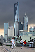 Pedestrians walk across a foot bridge with the skyscrapers of Pudong in the distance in Shanghai, China on 28 August 2010.  Investment in government infrastructure and real estate spending have surpassed foreign trade as the biggest contributor to China's growth, fueling fears of an economic slow down triggered by the debt burden.