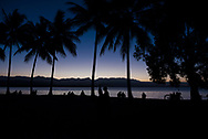 Beautiful blue-purple sky with palm trees and silhoutted people at sunset in Rex Smeal Park in Port Douglas, Australia.