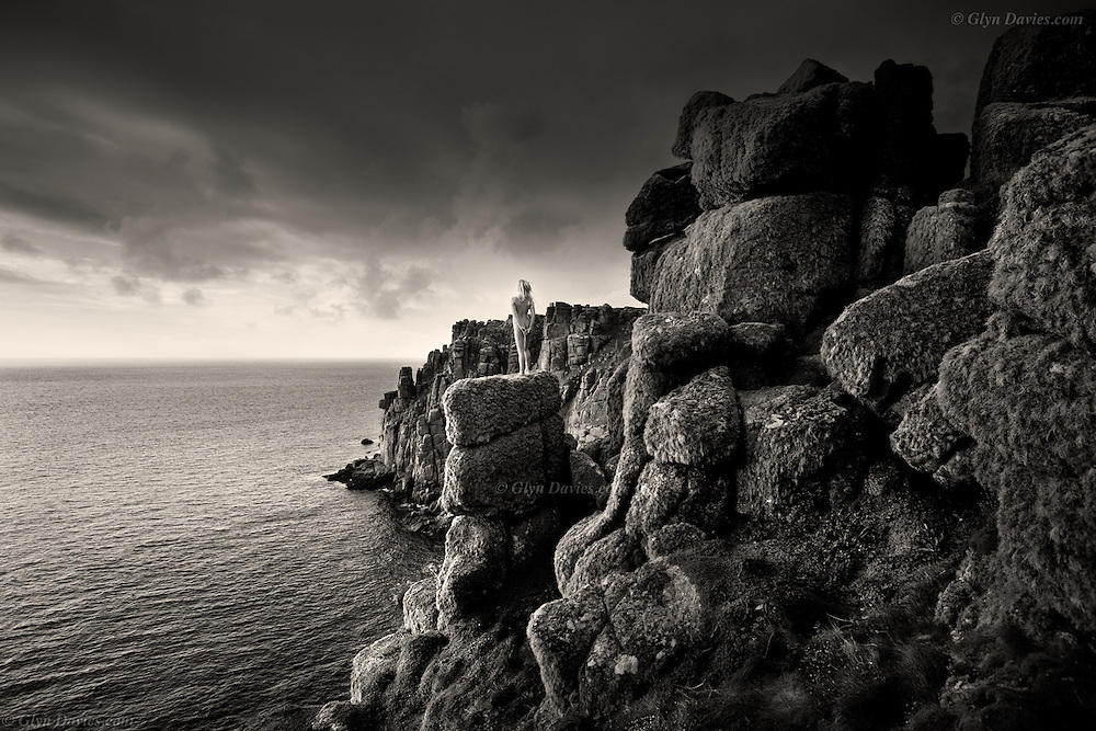On a high narrow pinnacle, hundreds of feet above the sea, backed by even larger towering cliffs behind, appears the tiny, fragile figure of a woman. Even though the wind is gusting, buffeting her, she stands resolutely facing the ocean. She is at the most westerly point of land and without assistance can go no further. She has reached a human boundary; the sea is not our domain. Cries of seagulls echo warnings in the nearby zawn.<br /> <br /> The sharp lichen thriving in the clean sea air covers every inch of the gritty platform on which she stands. She feels it digging into the soles of her feet as she ponders the vast expanse of water before her. Beyond that on the distant horizon, her Avalon, from where dreams have appeared to her in powerful waves.