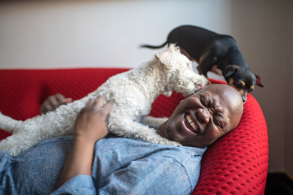 MANHATTAN, NY - MARCH 27, 2016: Tituss Burgess with his dogs Hanz, left, and Micah on his living room couch at home in Harlem. CREDIT: Emon Hassan