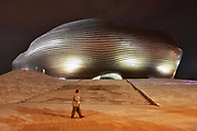 "A man walks past the slick Ordos Museum during night in Kangbashi New District of Ordos City, Inner Mongolia, China on 92 July, 2011. With an investment of over 161billion USD from the local government and revenue from the region's rich coal deposits, enough buildings have risen on the site of an old desert village to hold at least 300,000 residents, complete with ultra modern facilities and grand plazas. The district however is less than 10% occupied, dubbed the ""ghost city"", Kangbashi epitomizes China's real estate bubble and dangers in mindless investment fueled economic  growth. In 2011, the real estate price of Ordos city has dropped over 70%."