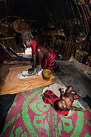 Dassanach tribe woman using a grindstone inside her hut, with her baby nearby, Omo Valley, Ethiopia.
