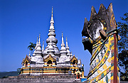 The central figure of the Manfeilang Monastery ( of the Dai denomination) is the White Pagoda  which lies on elevated ground on the banks of the Mekong river in south west Yunnan province.  Dai monasteries are built in the centre of a village or as in this case outside  on higher ground.<br /> <br /> Built in 1204, the Manfeilang monastery complex is in fact a cluster of nine pagodas or stupas, to enshrine what is purported to be the Buddha's footprint. The whole ensemble forms a fusion of Southeast Asian Buddhist style with typical Dai architecture. It is popular for Buddhist pilgrims from the surrounding region which attracts thousands during the Tan Ta Festival in late October early November each year.  In this region and in these Dai and Sino-Burmese monasteries, Theravada Buddhism is the religion that is practiced.