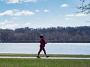"""29 MARCH 2020 - DES MOINES, IOWA: A person walks around Gray's Lake, a popular park and lake near downtown Des Moines. On Sunday morning, 29 March, Iowa reported 336 confirmed cases of the Novel Coronavirus (SARS-CoV-2) and COVID-19. There have been four deaths attributed to COVID-19 in Iowa. Restaurants, bars, movie theaters, places that draw crowds are closed until 07 April. The Governor has not ordered """"shelter in place""""  but several Mayors, including the Mayor of Des Moines, have asked residents to stay in their homes for all but the essential needs. People are being encouraged to practice """"social distancing"""" and many businesses are requiring or encouraging employees to telecommute.        PHOTO BY JACK KURTZ"""