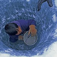 BAFFIN ISLAND, Nunavut, Canada. Inuit hunter, Jayko Apak (MR), chops fishing hole in frozen lake in Stewart Valley.