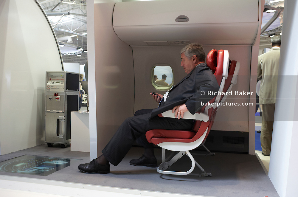 A delegate sends a text message from a mobile phone in a mock-up airliner cabin at the Paris Air Show exhibition at Le Bourget