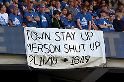 Huddersfield Town fans with a banner aimed at Paul Merson in the stands after the Premier League match at the John Smith's Stadium, Huddersfield.