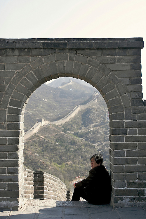 Resting half way up The Great Wall, a woman looks towards the rest of the climb at Badaling in China.