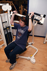 Woman using weights at an inclusive fitness gym,