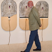 """VENICE, ITALY - MAY 28: Richard Armstrong director of the Solomon R Guggeheim Museum and Foundation walks in front of """"Four designs for a fountain in honur of the painter Balla"""" by Jim Dine at the press preview of Ileana Sonnabend """"Un Ritratto Italiano"""" on May 28, 2011 in Venice, Italy. The """"An Italian Portrait"""" Exhibition will be held in dedication to art dealer and collector Ileana Sonnabend, and presentsmore than 60 worksby Italian and international artists such as Pistoletto, Merz, Fontana, Manzoni, Rauschenberg, Koons, Sugimoto, Esser."""