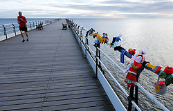 © Licensed to London News Pictures.<br /> 22/05/15<br /> <br /> Saltburn, UK. <br /> <br /> A man runs along the pier after the Saltburn Yarn Bombers struck again during the early hours of the morning and attached their latest creations to the railings on the pier at the beach. The knitted figures that represent, on the year marking the 150th anniversary, characters from Lewis Carroll's classic children's book Alice's Adventures in Wonderland are the latest creations from this group whose identities still remain a mystery.<br /> <br /> Photo credit : Ian Forsyth/LNP