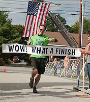 WOW Fest 2013 runner crossing the finish line at Laconia Athletic and Swim Club.   (Karen Bobotas/for the Laconia Daily Sun)