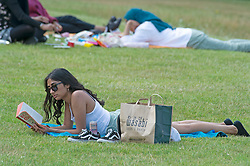 © Licensed to London News Pictures 23/07/2021. Greenwich, UK. A woman relaxing with a good book. People making the most of a heatwave afternoon in Greenwich park, London before a weekend of torrential rain and thunderstorms spoil the nice weather party.<br /> Photo credit:Grant Falvey/LNP