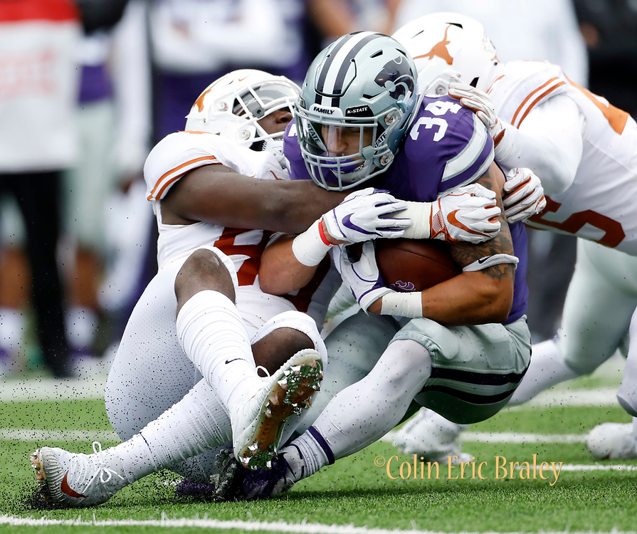 Kansas State running back Alex Barnes (34) is tackled by Texas defensive lineman Charles Omenihu (90) and linebacker Anthony Wheeler (45) during the first quarter of a college football game in Manhattan, Kan., Saturday, Sept. 29, 2018. (AP Photo/Colin E. Braley)