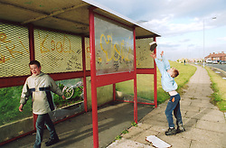 Boys playing in bus shelter; Bradford council estate; UK, Boy throwing lump of cement