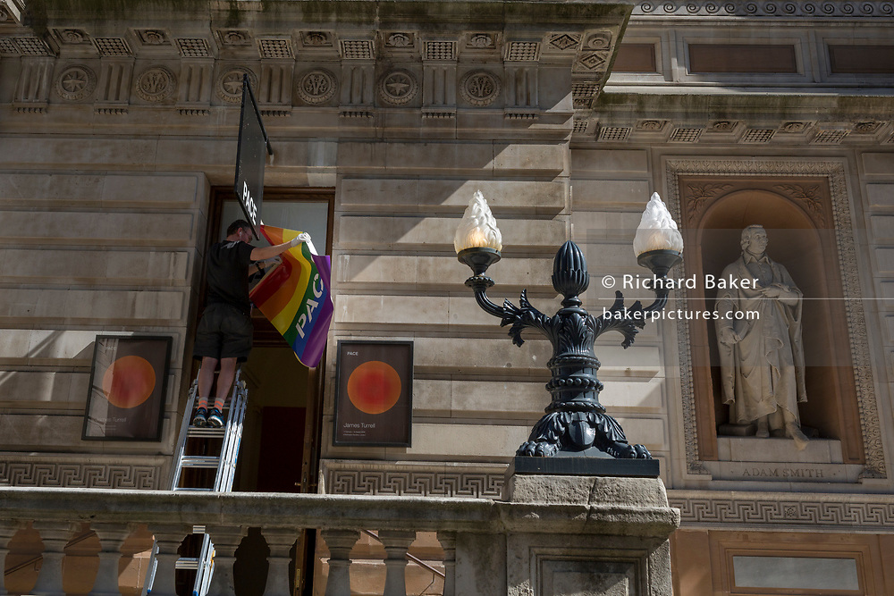 With a further 184 reported UK Covid deaths in the last 24 hrs, a total now of 43,414, a museum employee positions a poster for the annual LGBT Pride event at the Pace gallery in the Royal Academy. Pride 2020 has been cancelled because of the Coronavirus pandemic, on 26th June 2020, in London, England. Government restrictions are expected to ease for art galleries like the RA, with plans to re-open on 4th July. Venues re-opening will be conditional on the progression of the virus and how well social distancing measures are implemented.
